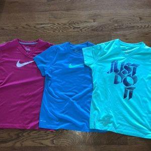 blue, mint green, and pink nike dri-fit t-shirts.